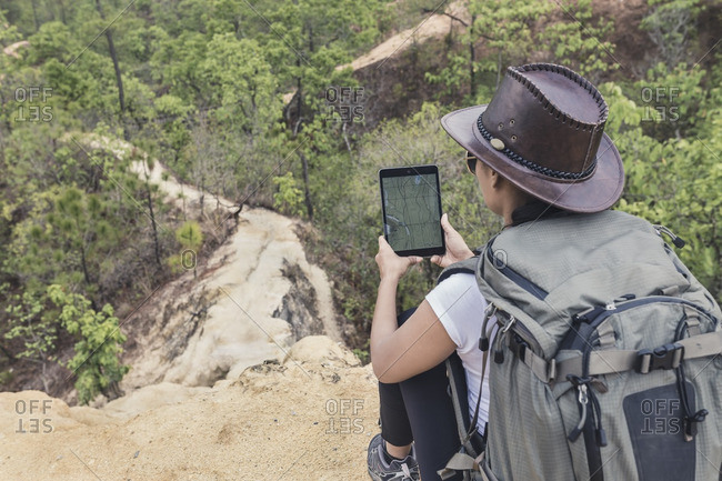 Woman with tablet on mountain overlook