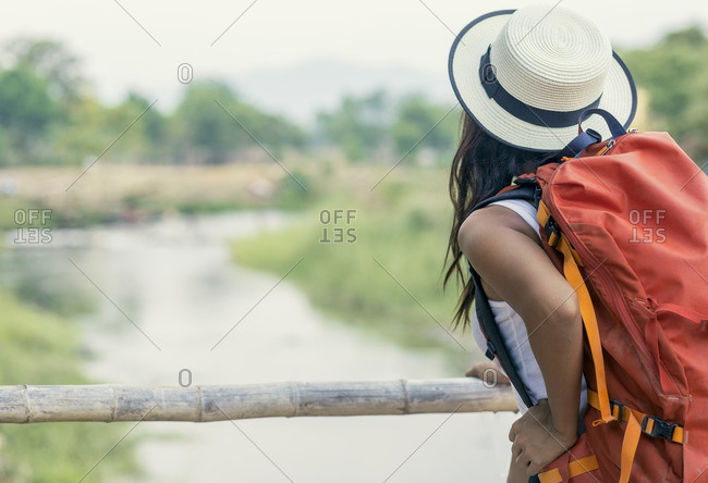 Backpacker looking at view of river