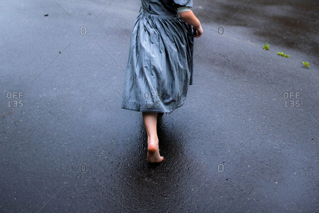 Girl walking barefoot on a wet road