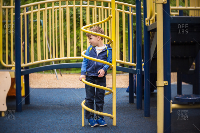 Boy standing inside a metal spiral on a playground