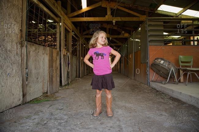 Girl in horse shirt in a barn