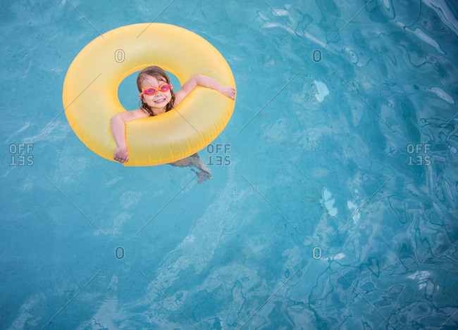 Girl in a yellow ring in the blue pool
