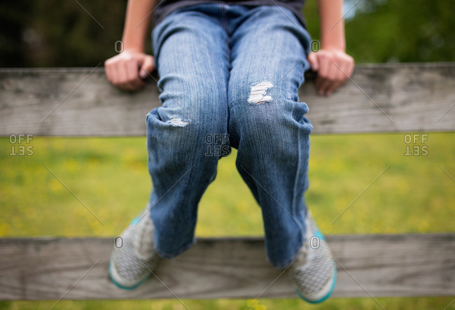 Boy in jeans with holes in the knees
