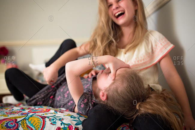 Girl lying on each other, laughing in bed