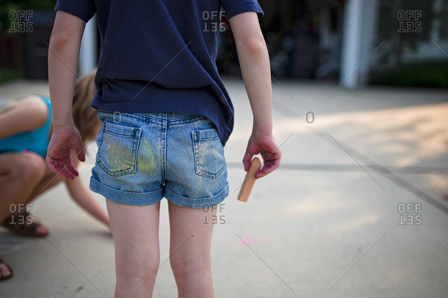 Girl with chalk in hand and over her pants