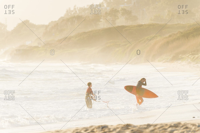 4/1/13: Two surfers standing along a beach in Tarifa, Spain