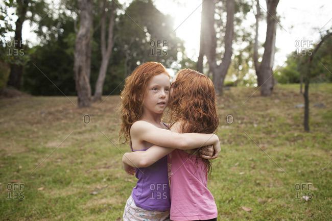Two young girls hugging in a garden
