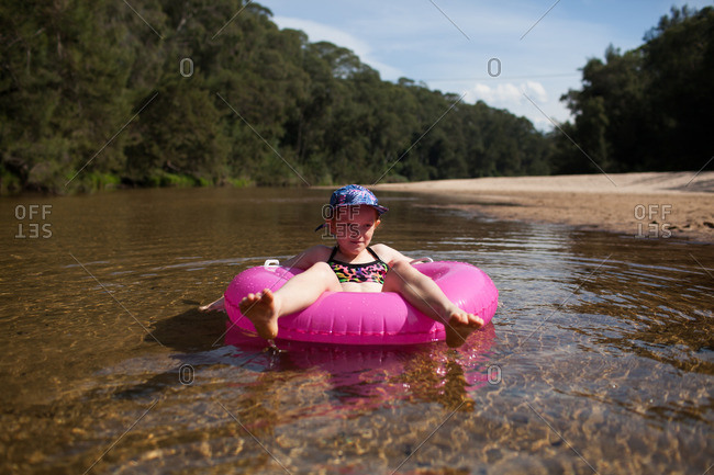 Young girl floating on a river in an inflatable ring