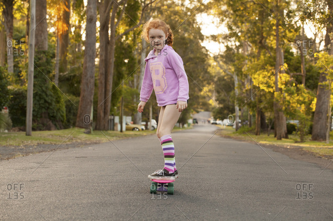 Young girl riding a skateboard in the street