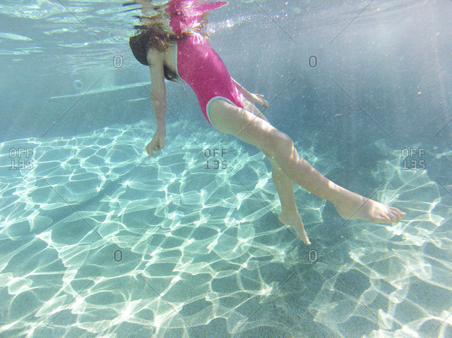 Young girl floating underwater in a swimming pool