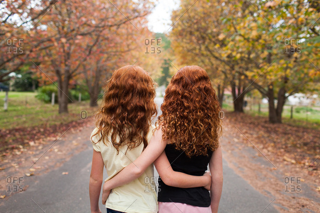 Two redhead girls hugging in a street