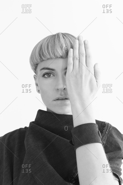 Stylish woman covering half of her face with her hand