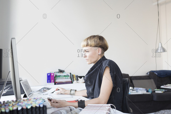 Young woman in a denim shawl working at a desk