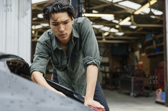Young man working on a car at a metal shop