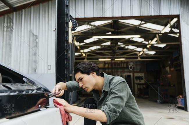 Young man repairing a car at a metal shop