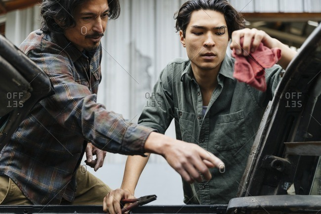 Two men working on a car at a repair shop