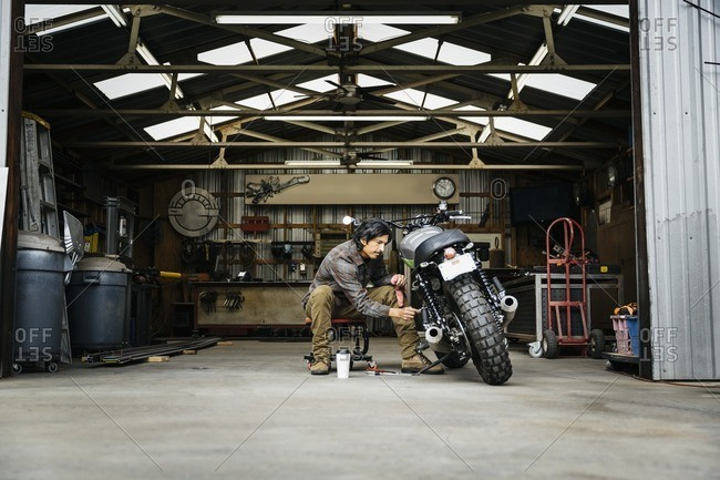 Man working on a motorcycle in a repair shop