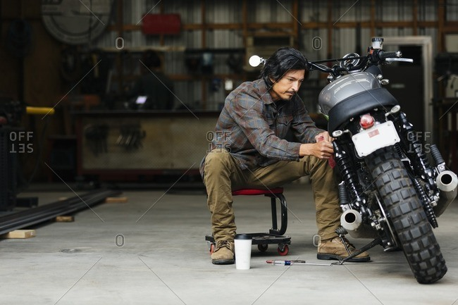 Man repairing a motorcycle in an automotive shop