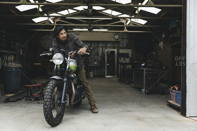 Man sitting on a motorcycle in an automotive repair shop