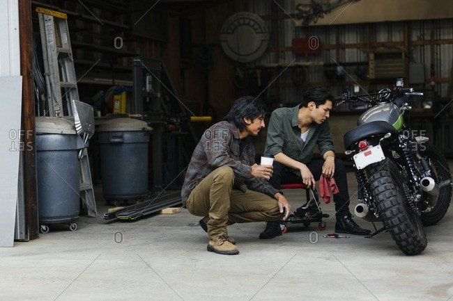 Two men working on a motorcycle in a repair shop