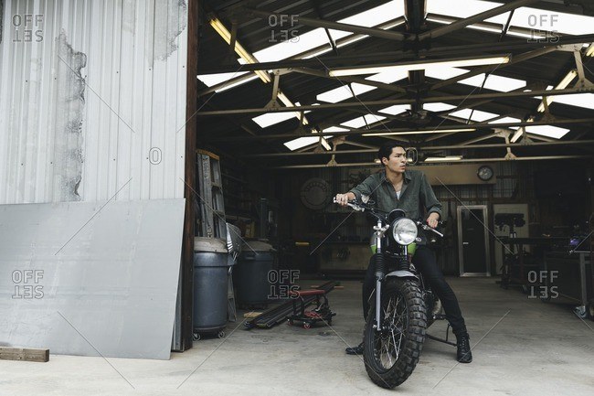 Young man sitting on a motorcycle in a workshop