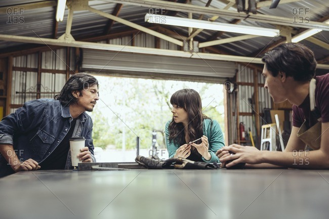 Three people having a conversation around a table in a metal shop