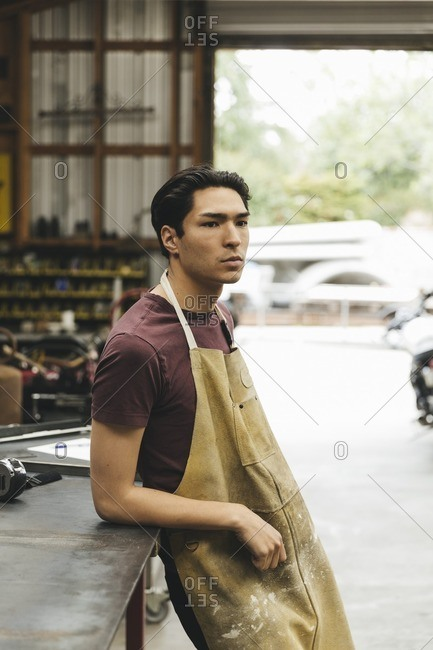 Young man leaning against a table in a mechanic shop