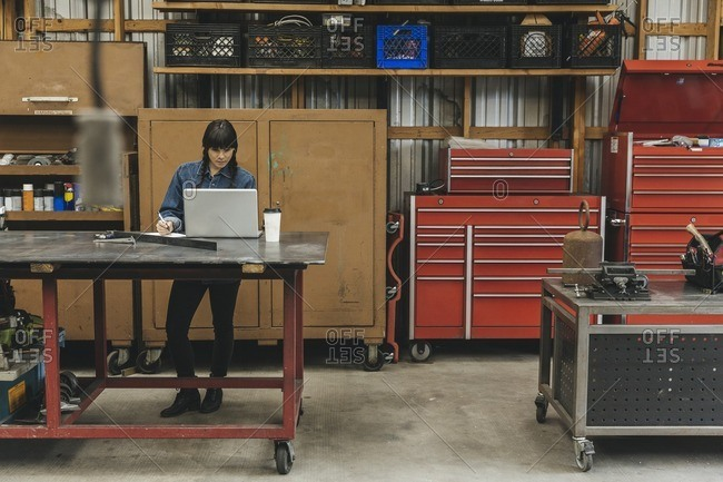 Young woman working at a computer in a mechanic shop