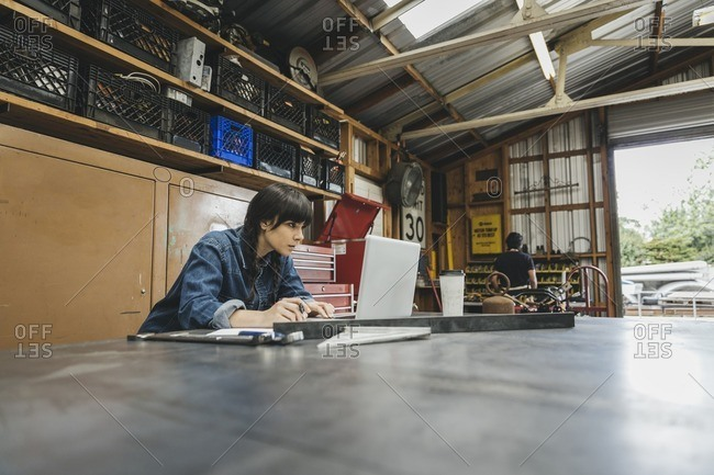 Young woman working on a laptop in a repair shop