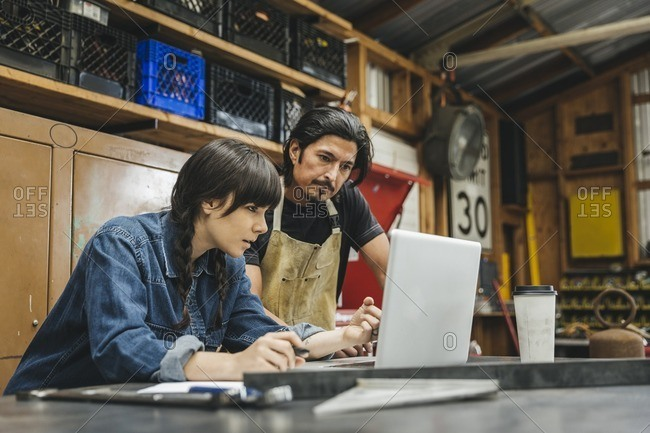 Man and woman working at a computer in a repair shop