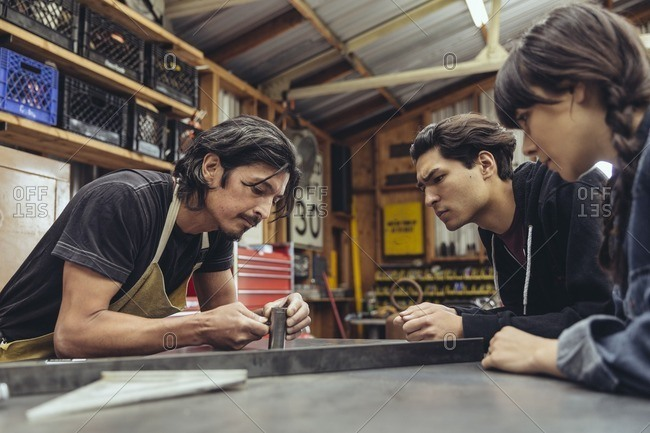 Three people assembling a part in a metal shop
