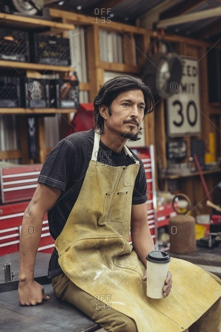 Man sitting on a table drinking coffee in a repair shop
