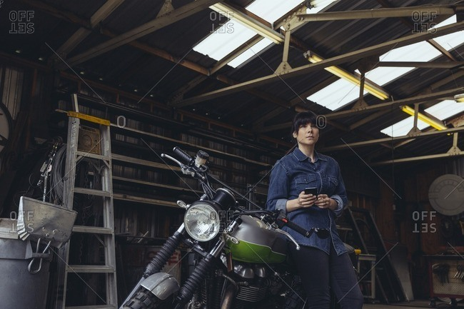 Woman leaning against a motorcycle while using her phone in a metal shop