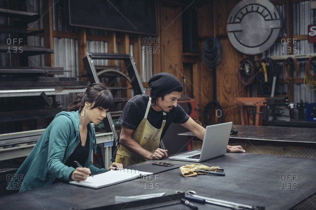Man and woman working together at a computer in a mechanic shop