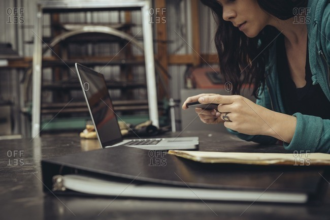 Young woman working on a phone and laptop in a mechanic shop