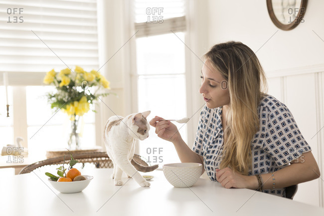 Woman eating out of bowl while talking to cat