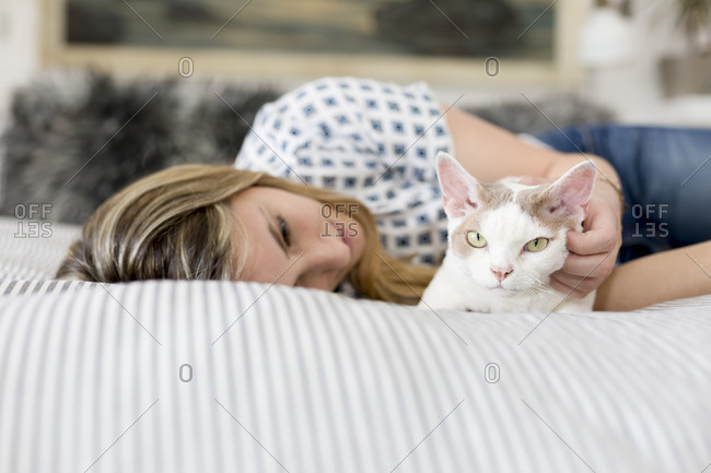 Woman petting her cat while lying on bed