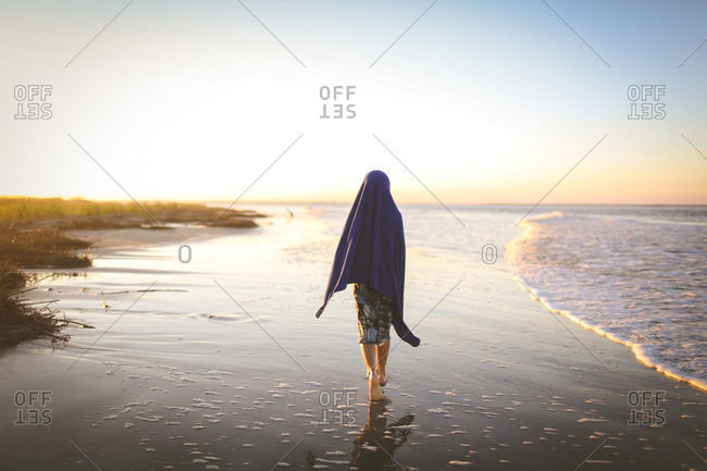 Child on beach draped in towel