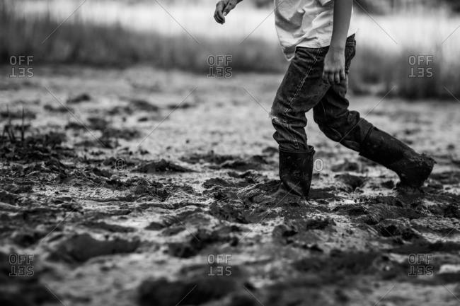 Child walking in muddy field