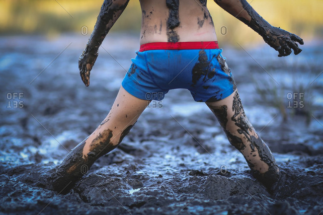 Child standing in the mud