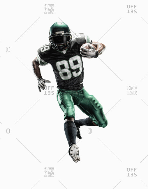 Studio shot of young male football player running with ball