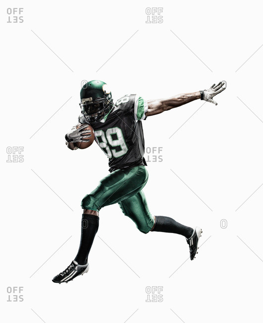 Studio shot of male football player running with ball