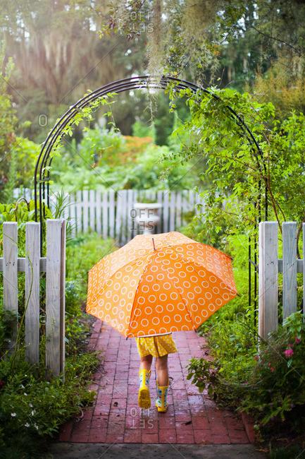 Girl walking through garden gate carrying umbrella