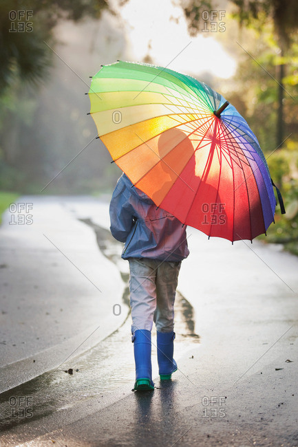 Rear view of boy carrying umbrella on street