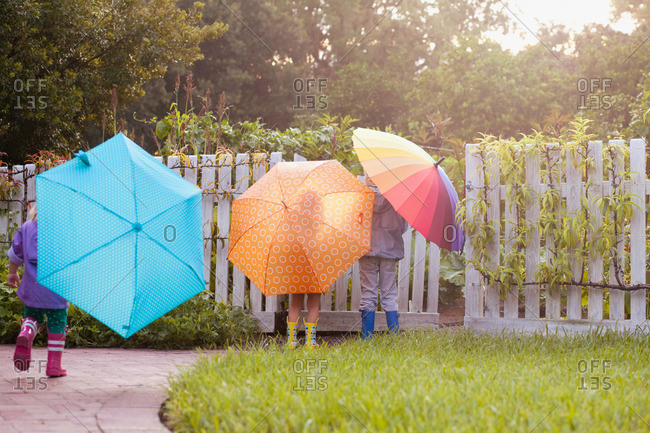 Boy and two sisters playing in garden carrying umbrellas