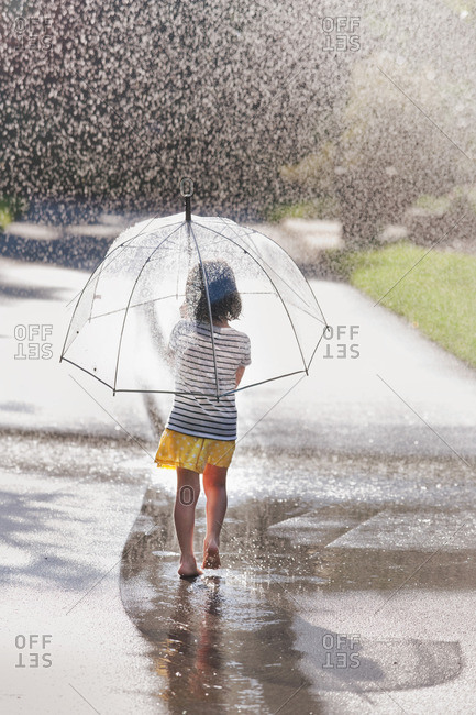 Rear view of barefoot girl carrying umbrella walking through street puddle