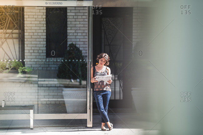 Young woman at bus stop reading newspaper and waiting for bus