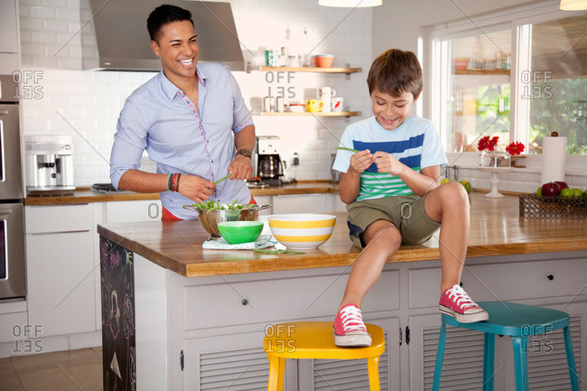 Father and son in kitchen, boy sitting on counter