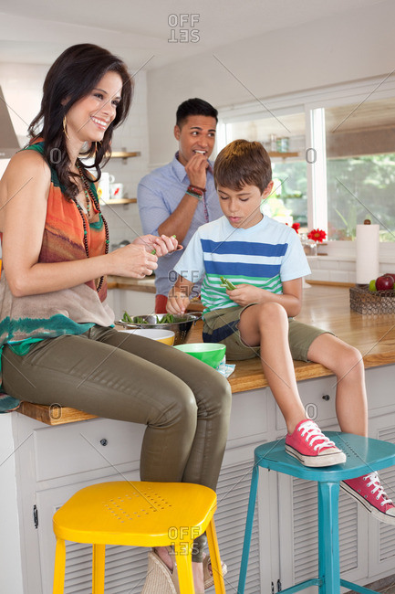 Boy sitting on kitchen counter with mother and father
