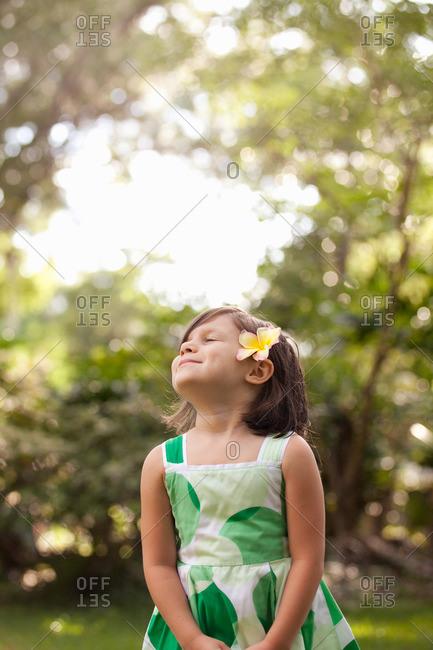 Young girl in garden, wearing flower in her hair